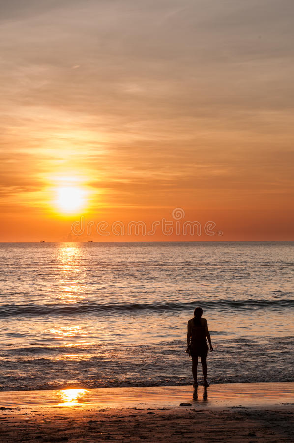 Spiaggia di tramonto con una giovane donna immagine stock