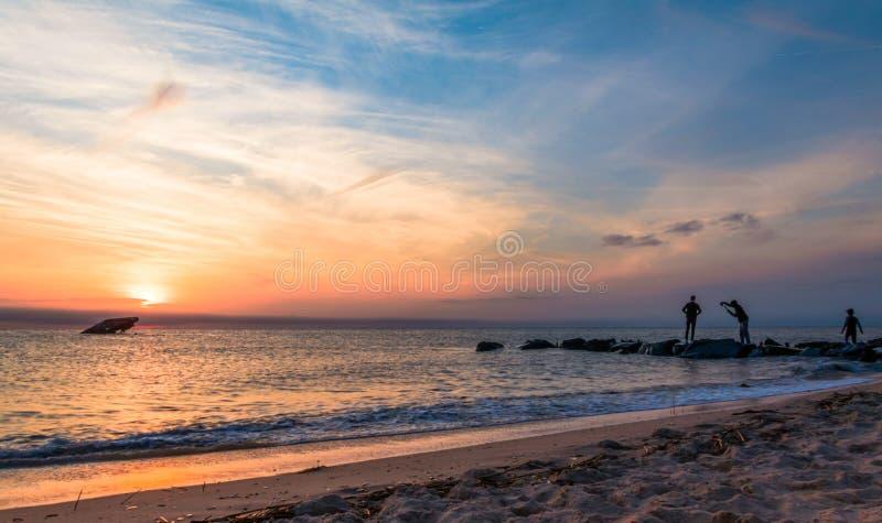 Spiaggia di tramonto in molla in anticipo con i giovani maschi che posano per le foto nella distanza - punto NJ di Cape May fotografia stock libera da diritti