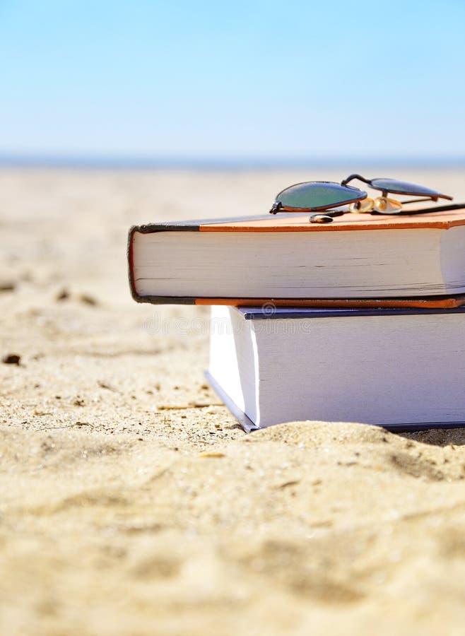 Spiaggia di vacanza con i libri in sabbia fotografie stock libere da diritti