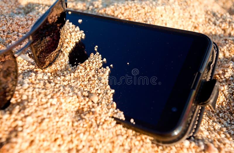 Spiaggia di vacanza della sabbia dello Smart Phone fotografie stock libere da diritti