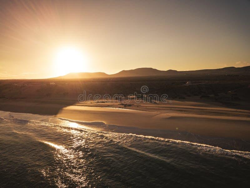 Spiaggia e oceano durante l'alba o il tramonto con il sole dietro le montagne sullo sfondo - bellissima vista aerea della natura fotografia stock