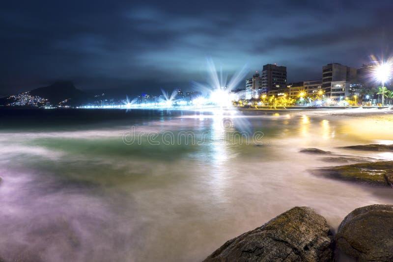 Spiaggia famosa di Ipanema alla notte con le belle luci e le onde di acqua lente sopra le rocce fotografie stock libere da diritti