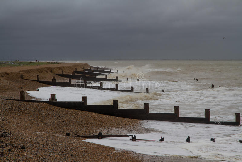 Spiaggia inglese tempestosa con i frangiflutti fotografia stock
