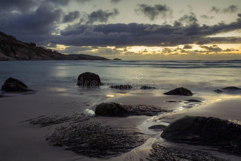 Spiaggia isolata sotto un cielo drammatico di tramonto immagini stock
