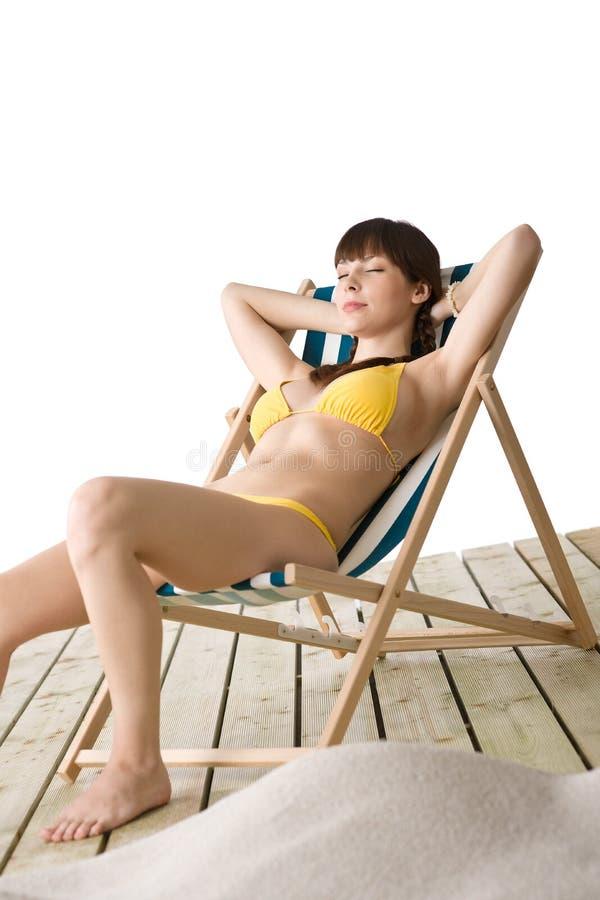 Spiaggia - la donna si distende in bikini su deckchair immagini stock libere da diritti