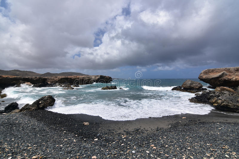 Spiaggia nera della pietra della sabbia in Aruba con le onde che vengono a terra immagine stock libera da diritti