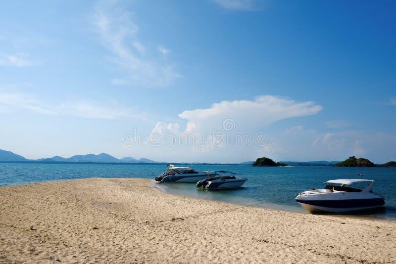 Spiaggia piena di bellezza e la barca di tre velocità immagini stock