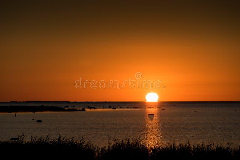 Spiaggia rocciosa di tramonto, mare pacifico, cielo arancio Kihnu, piccola isola in Estonia immagine stock libera da diritti