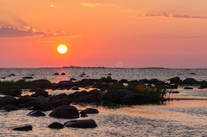 Spiaggia rocciosa di tramonto, mare pacifico, cielo arancio Kihnu, piccola isola in Estonia Mar Baltico, Europa Fondo dell'ambien fotografie stock