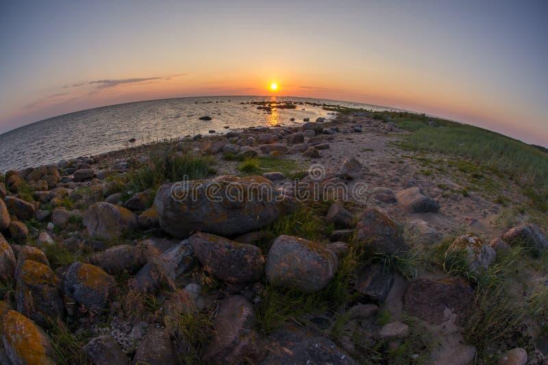Spiaggia rocciosa di tramonto, mare pacifico, cielo arancio Kihnu, piccola isola in Estonia Mar Baltico, Europa Fondo dell'ambien immagini stock libere da diritti