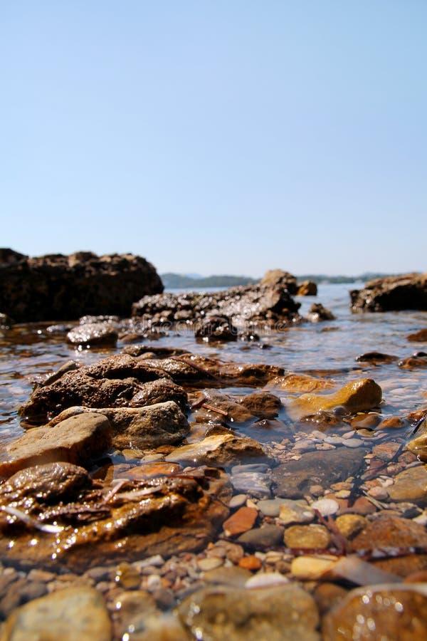 Spiaggia rocciosa esotica con le pietre variopinte, mare blu tropicale con le onde e schiuma Bello ambiente naturale, panorama, p fotografia stock