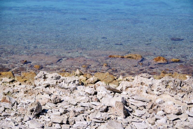 Spiaggia rocciosa esotica, mar Mediterraneo blu tropicale con le onde e schiuma del mare Bello ambiente naturale, panorama, paesa immagini stock libere da diritti