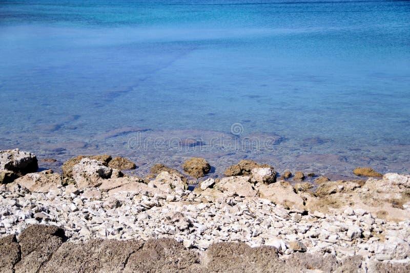 Spiaggia rocciosa esotica, mar Mediterraneo blu tropicale con le onde e schiuma del mare Bello ambiente naturale, panorama, paesa fotografie stock