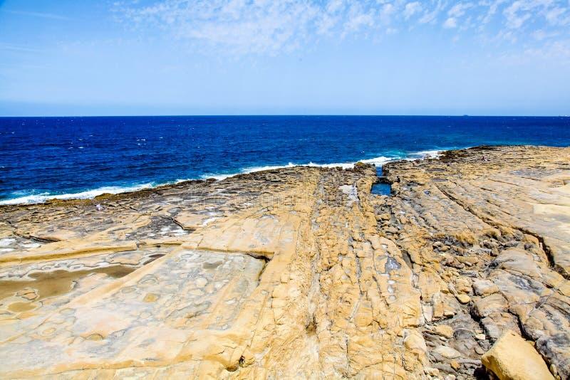 Spiaggia rocciosa stupefacente in Sliema, Malta un giorno soleggiato immagini stock libere da diritti
