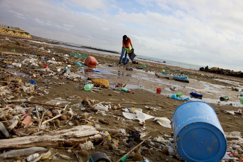 Spiaggia sporca pulita della donna terribile di disastro ecologico fotografia stock libera da diritti