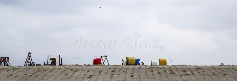 Spiaggia tedesca tipica con i sedili ed il campo da giuoco di riposo fotografia stock