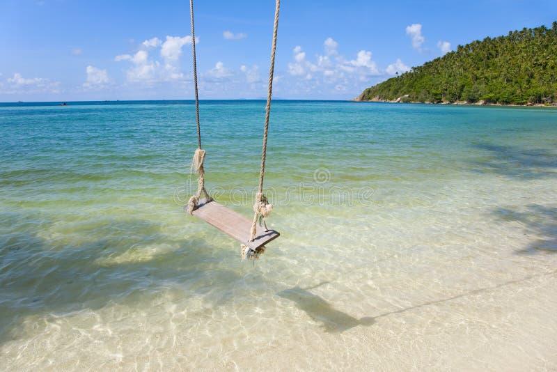 Spiaggia tropicale con le palme di noce di cocco e la vecchia oscillazione fotografia stock