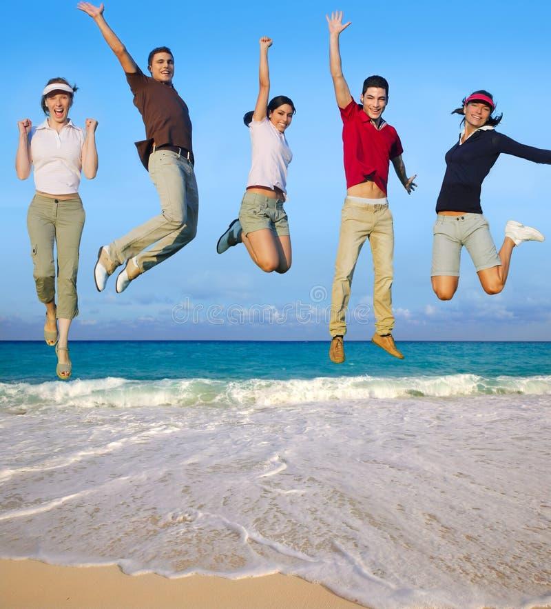 Spiaggia tropicale di salto del gruppo felice dei giovani immagini stock libere da diritti