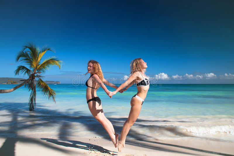 Spiaggia tropicale, donne divertendosi, simbolo del cuore di amore di salto fotografie stock