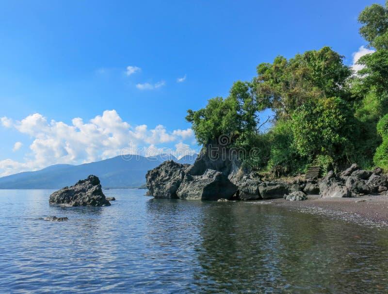 Spiaggia vergine romantica con la sabbia nera Formazioni rocciose dell'origine vulcanica le scogliere delle forme astratte sporgo fotografia stock