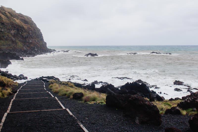 Spiaggia vulcanica della sabbia nera con la schiuma del mare bianco nelle isole delle Azzorre fotografia stock