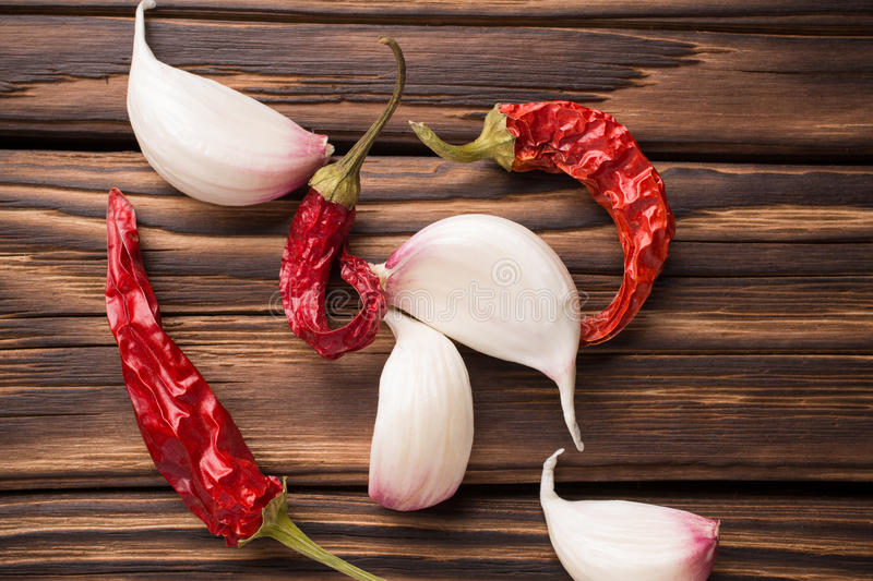 Spice. Garlic with red chili pepper on wooden background royalty free stock photography