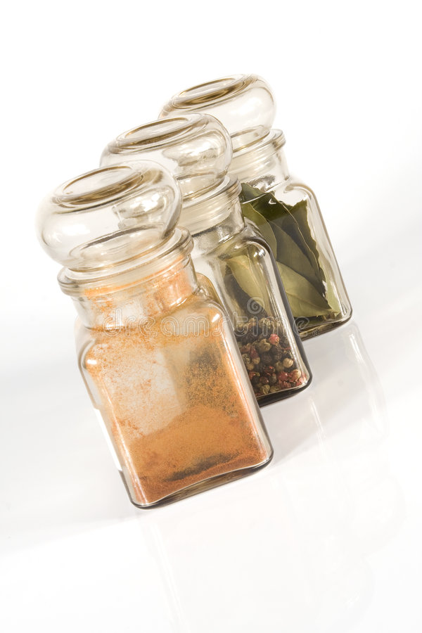 Spice Jars. On gray light (white) background; bay-leaf, pepper (4 colours), paprika royalty free stock photography