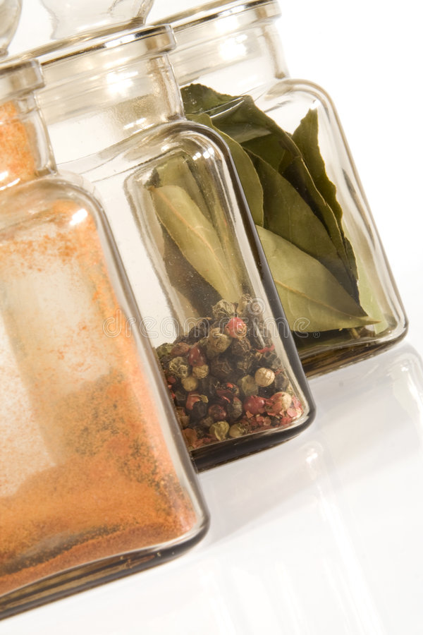 Spice Jars. On gray light (white) background; bay-leaf, pepper (4 colours), paprika royalty free stock photo