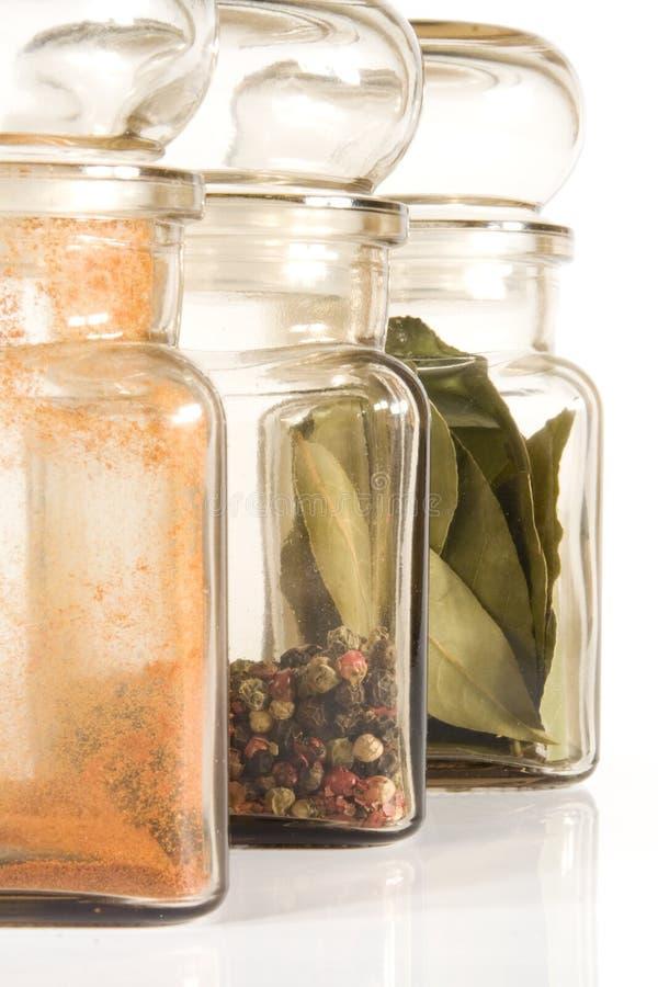 Spice Jars. On gray light (white) background; bay-leaf, pepper (4 colours), paprika stock photo