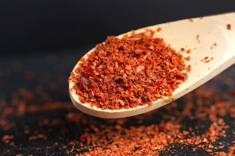 Spice red, ground, sharp bitter pepper is pouring out, a shovel is flying from a wooden scoop. Dark background.  royalty free stock images