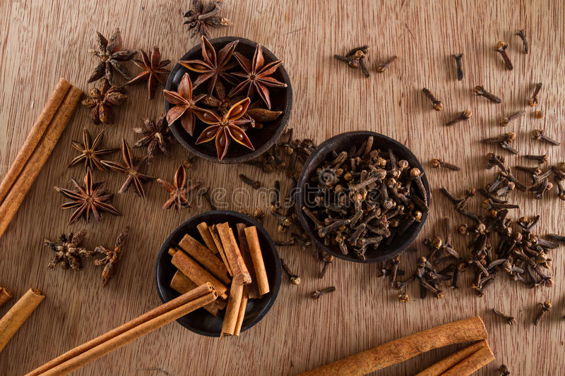 Spices. Assorted spices for food and decoration, against a rustic wooden background: cinnamon, star anise, cloves. Copy space royalty free stock photos