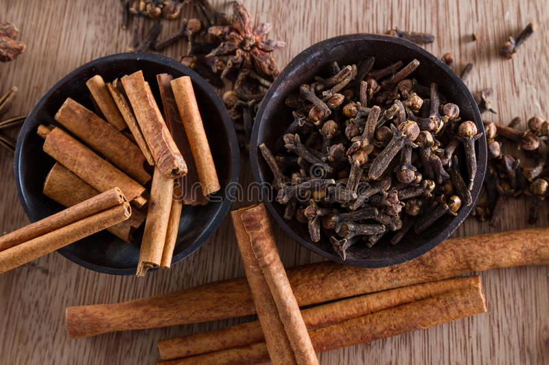 Spices. Assorted spices for food and decoration, against a rustic wooden background: cinnamon, star anise, cloves. Copy space royalty free stock photo