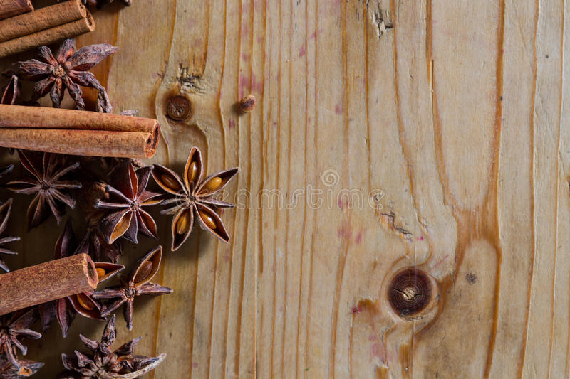Spices. Assorted spices for food and decoration, against a rustic wooden background: cinnamon, star anise, cloves. Plenty of copy space royalty free stock images