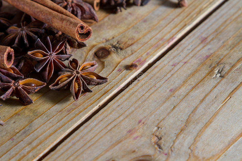 Spices. Assorted spices for food and decoration, against a rustic wooden background: cinnamon, star anise, cloves. Plenty of copy space stock photos
