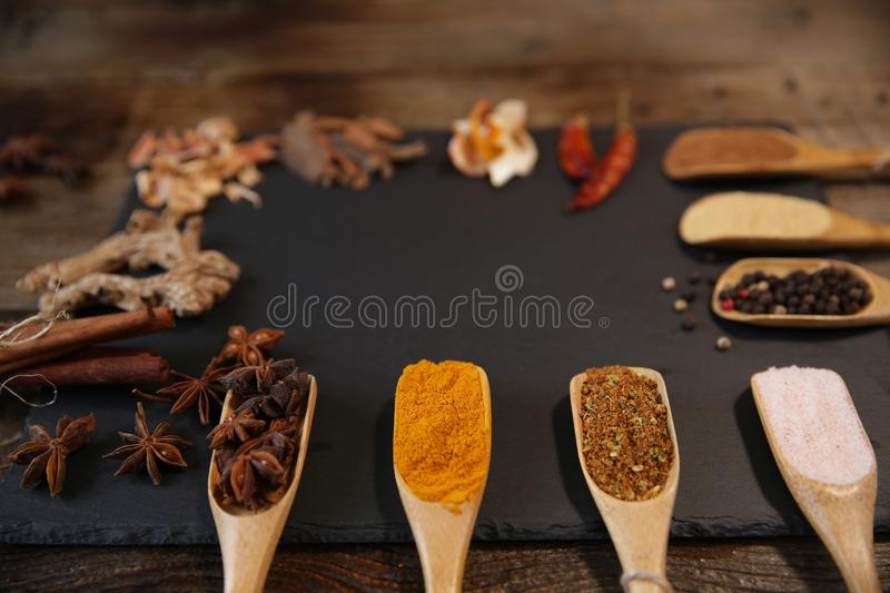 Spices assortment: turmeric, ginger, cinnamon, nutmeg, pepper, pink salt, star anise in wooden spoons on a black background. stock image