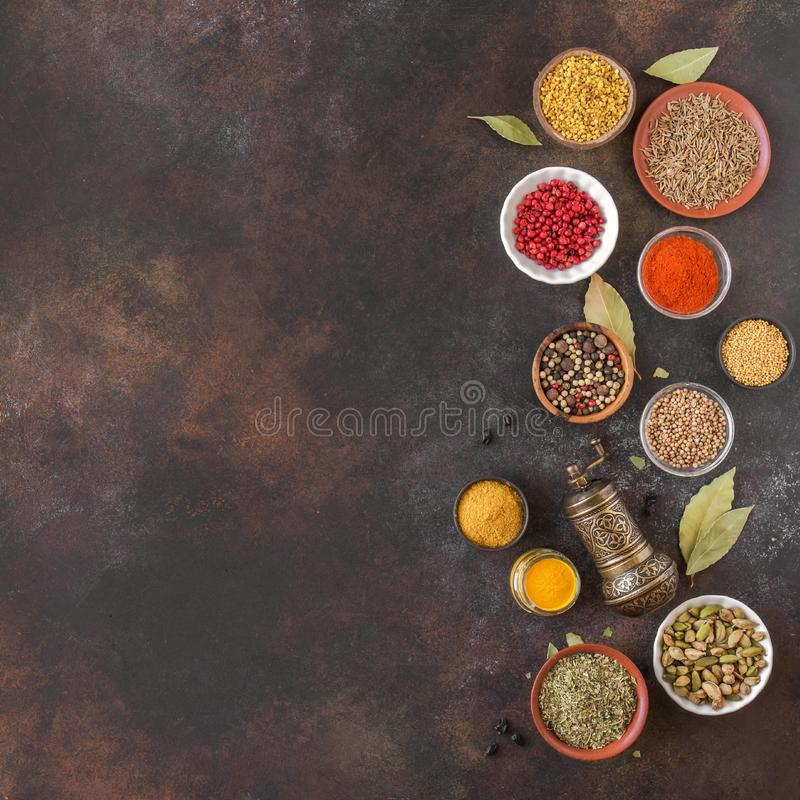 Spices Assortment. Various Spices on dark background. Assortment, set of spices and condiments with pepper mill, top view, copy space. Cooking food concept royalty free stock photography