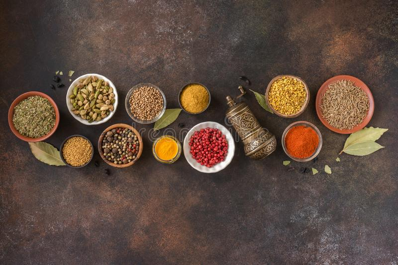 Spices Assortment. Various Spices on dark background. Assortment, set of spices and condiments with pepper mill, top view, copy space. Cooking food concept stock photo