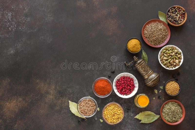 Spices Assortment. Various Spices on dark background. Assortment, set of spices and condiments with pepper mill, top view, copy space. Cooking food concept stock photography