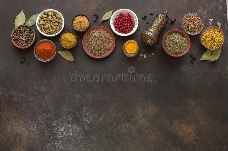 Spices Assortment. Various Spices on dark background. Assortment, set of spices and condiments with pepper mill, top view, copy space. Cooking food concept royalty free stock photo