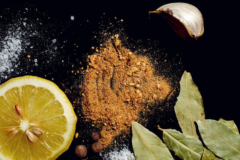 Spices on black background. Herbs and spices on an old black metal pan royalty free stock images