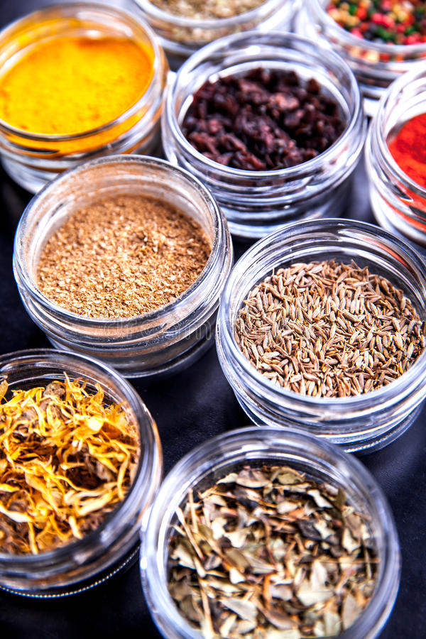 Spices on black background in special jars. Food royalty free stock photo