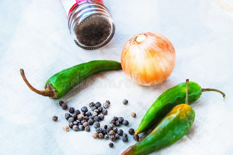Spices black pepper and hot green peppers with onions on a linen cloth on the kitchen stock photo