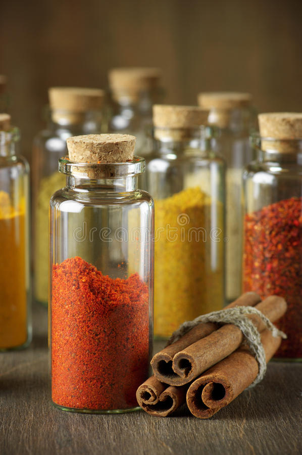Spices in bottles. Assorted ground spices in bottles and cinnamon sticks on wood stock photography