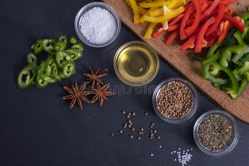 Spices, chopped paprika and spices on a wooden board. On a black background royalty free stock images