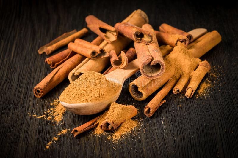 Spices; cinnamon sticks and ground in a wooden spoon on a dark background stock photo
