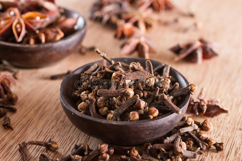 Spices: cloves. Spices series: a bowl full of cloves against a wooden background. Copy space royalty free stock photos