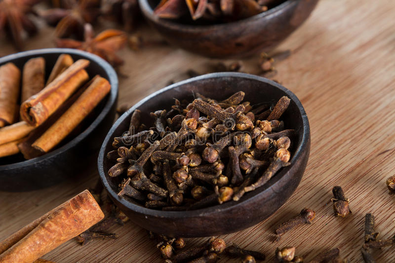 Spices: cloves. Spices series: a bowl full of cloves against a wooden background. Copy space. Cinnamon and star anise blurred in the background royalty free stock images