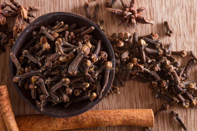 Spices: cloves. Spices series: a bowl full of cloves against a wooden background. Copy space. Star anise and cinnamon sticks on the background stock photo