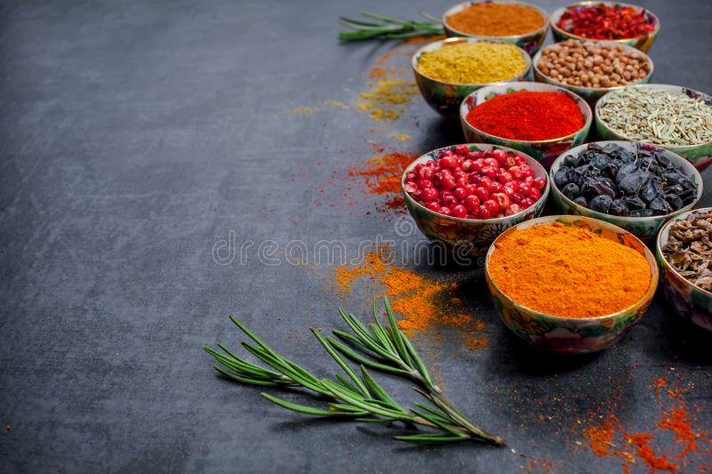 Spices. Colorful spices. Curry, Saffron, turmeric, cinnamon and otheron a dark concrete background. Pepper. Large collection of di. Fferent spices and herbs royalty free stock photography