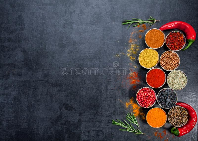 Spices. Colorful spices. Curry, Saffron, turmeric, cinnamon and otheron a dark concrete background. Pepper. Large collection of di. Fferent spices and herbs stock photo